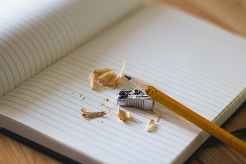 A broken pencil on a blank notebook