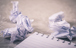 crumpled paper next to spiral notepad